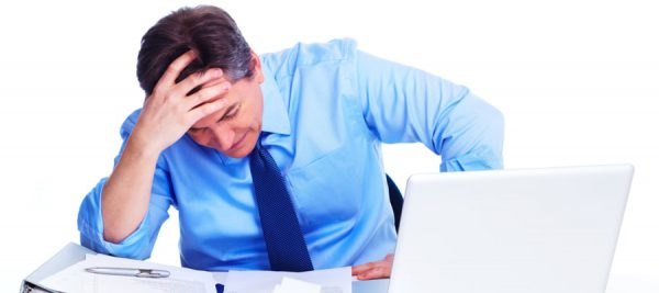 man sitting at desk in anguish